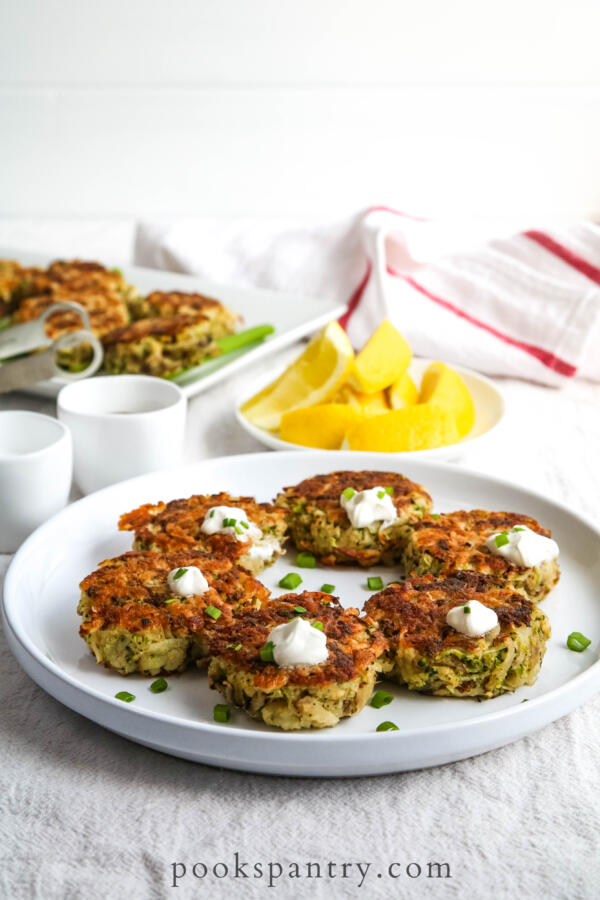 Potato broccoli cakes on white plate with lemon wedges in the background.