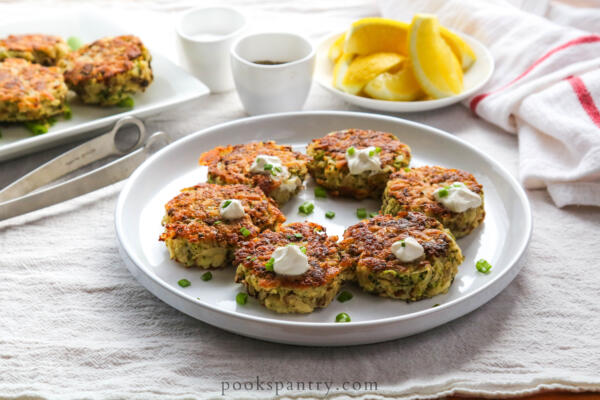 potato cakes with sour cream and chives on white plate