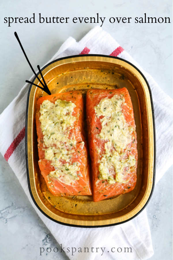 butter on top of raw salmon in container