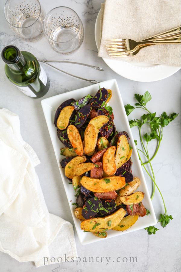 duck fat fingerling potato recipe on platter with herbs and napkin