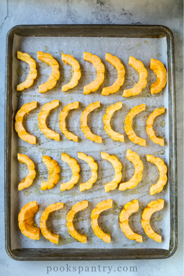 slices of delicata squash on a sheet pan, ready to roast.