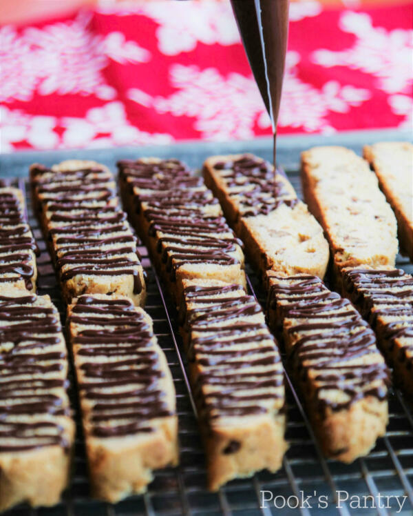 drizzling chocolate on butter pecan biscotti