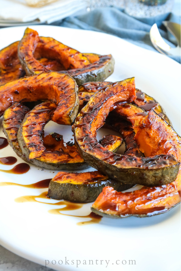 roasted Hubbard squash on white platter drizzled with maple vinaigrette