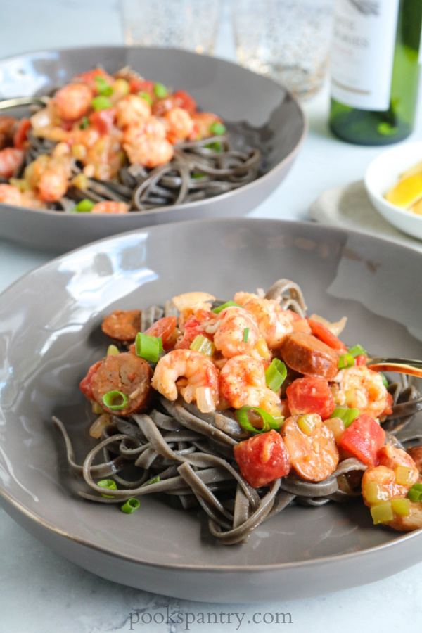 cajun langostino pasta with squid ink noodles in shallow gray bowls