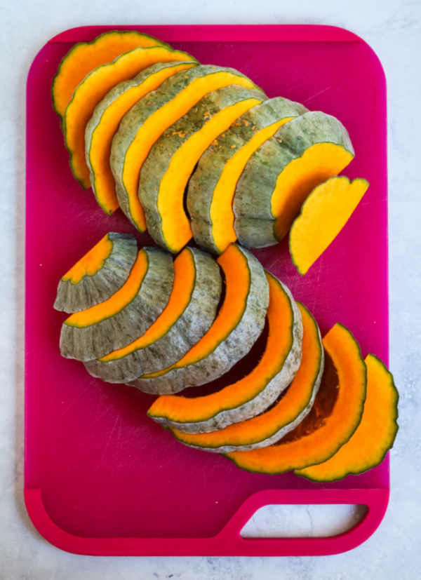 sliced Hubbard squash on pink cutting board