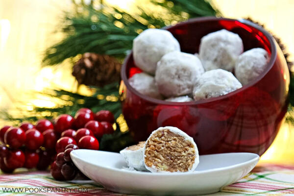 Easy rum balls recipe cut in half on white plate with bowl of rum balls in background.