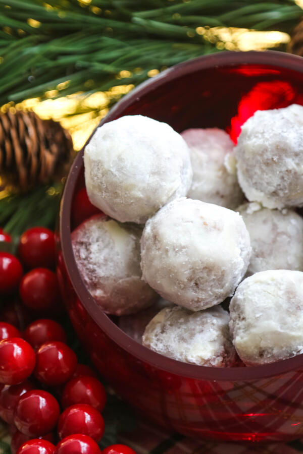 Christmas rum balls in red bowl with pine tree in background.