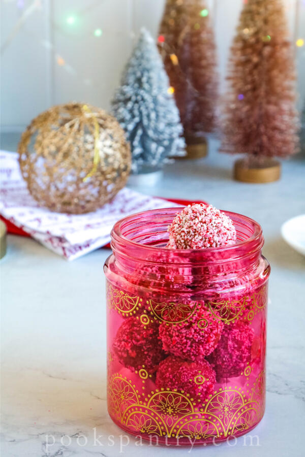rum balls with peppermint for gifting in pink glass jar.