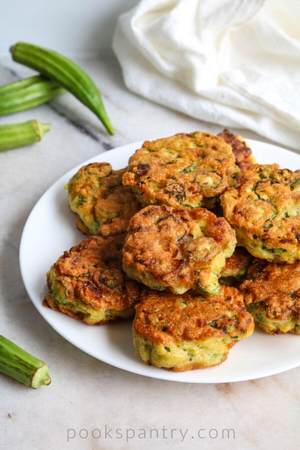 fried okra cakes piled on a white plate