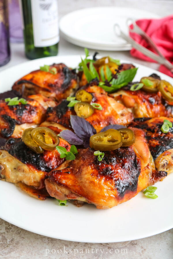 chicken thighs with bourbon and jalapeños on white platter