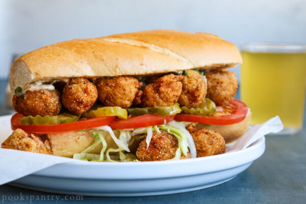 fried langostino po' boy on white plate with beer in background