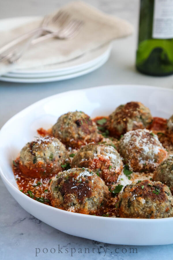 beef meatballs in white bowl with tomato sauce and parsley