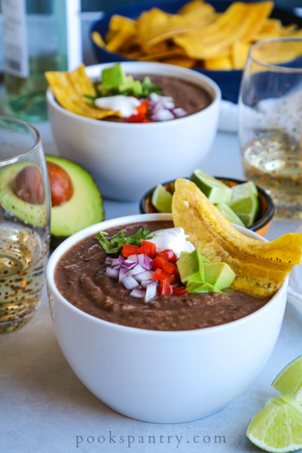 Instant pot black bean soup with dried beans, plaintain chips, avocado and onion garnish.