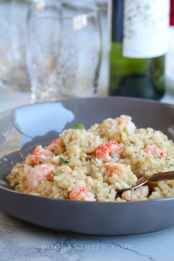 langostino risotto is gray bowl with herbs and gold spoon