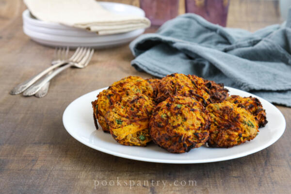 air fried butternut squash fritters with forks, plates and napkin
