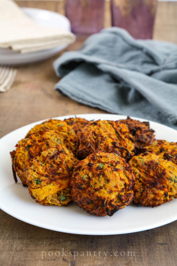 butternut squash fritters on white plate with blue napkin in background