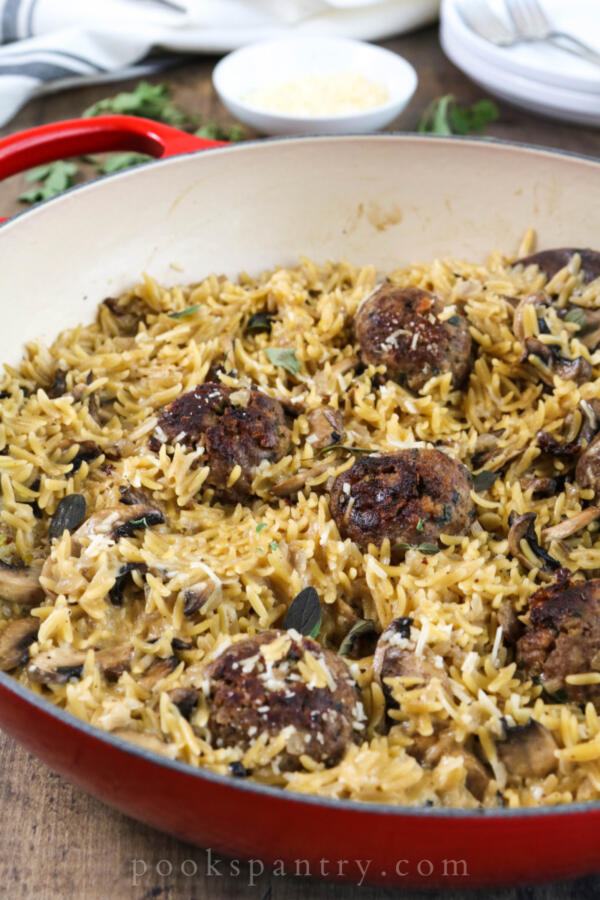 Mushroom orzo with meatballs in a red pan with parmesan and herbs