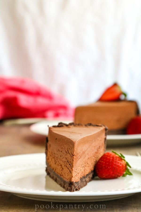slice of no bake chocolate cheesecake on white plate with strawberry