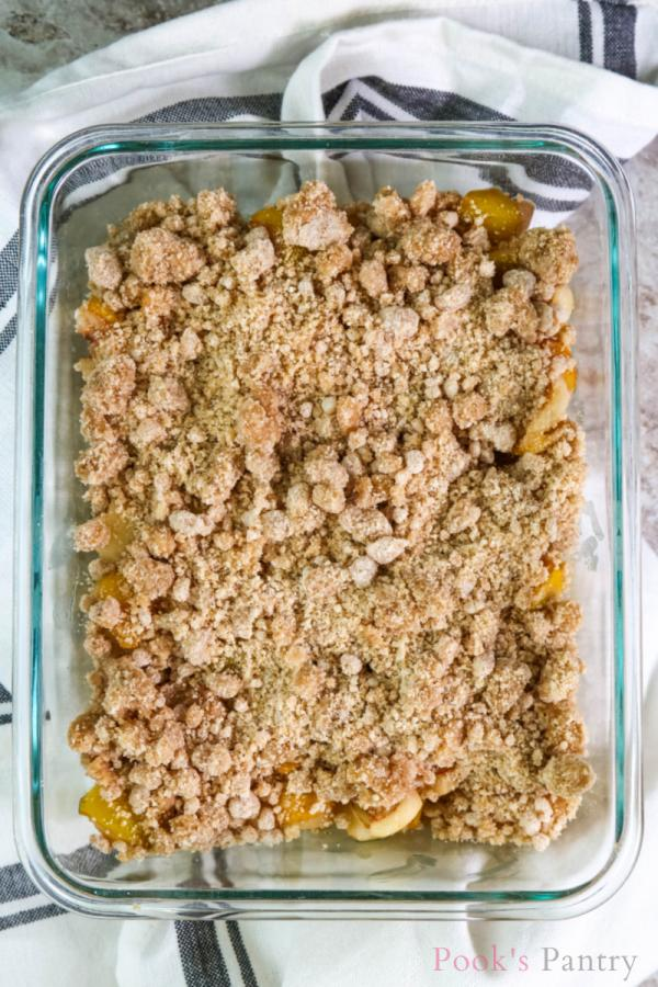 Crumble topping on top of loquats in glass dish
