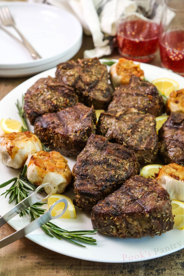 Lamb T-bones with garlic, lemon and rosemary on white platter with heads of roasted garlic