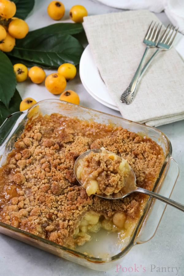 loquat crumble in glass baking dish with antique spoon