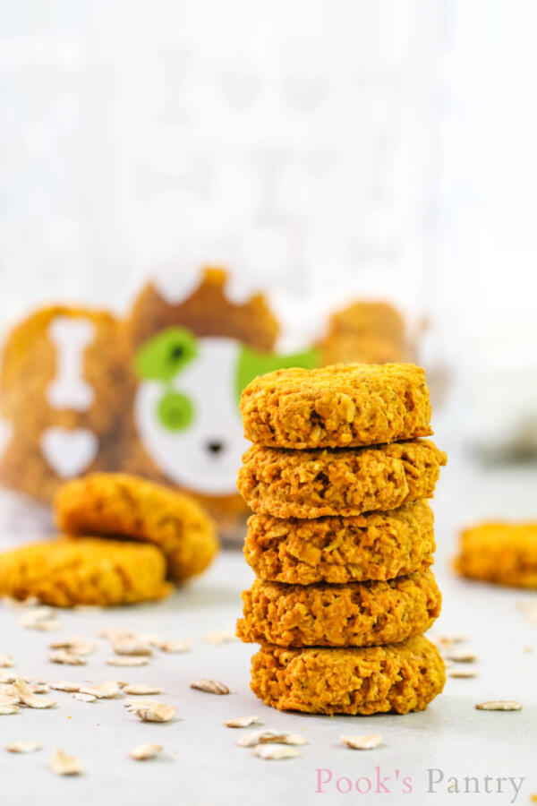 stacked pumpkin turmeric dog treats with oatmeal on marble countertop