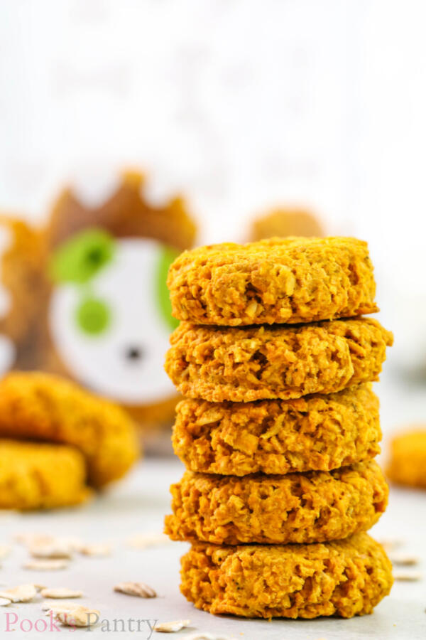 Pumpkin turmeric dog treats stacked on top of each other with oats in the background on a white marble board.