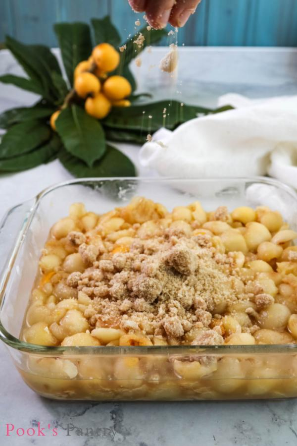 sprinkling crumble topping over loquat crumble in glass dish