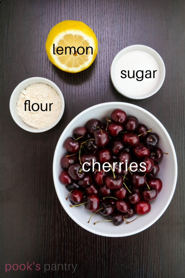 Ingredients for cherry crisp on dark brown background.