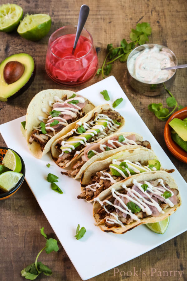 Chicken tacos with cumin lime crema, pickled radishes and avocado on white platter with wood background.