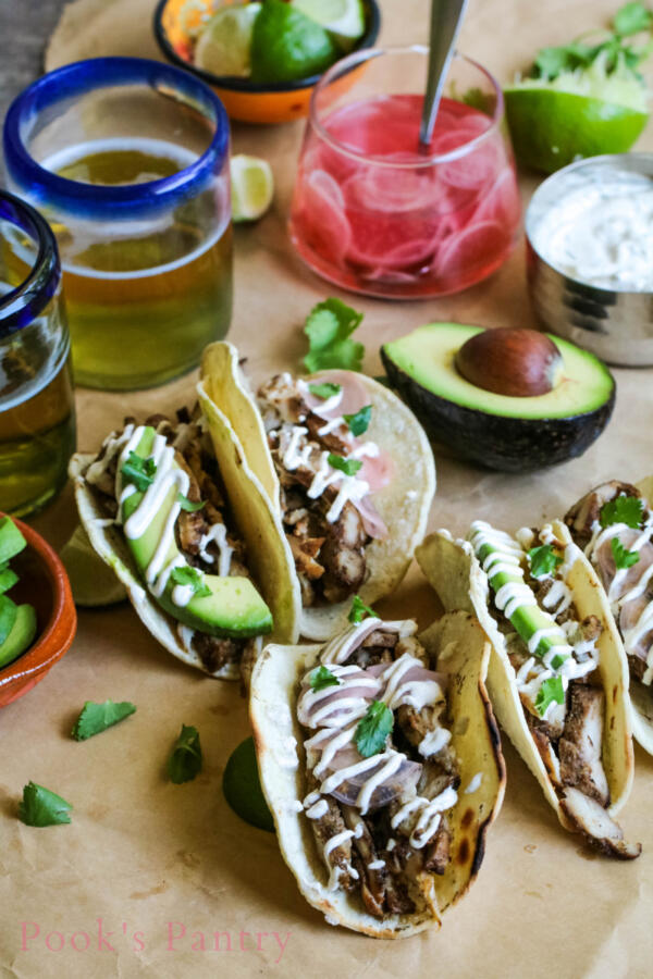 Grilled tacos with chicken and lime crema on butcher paper with avocados and beer in the background.