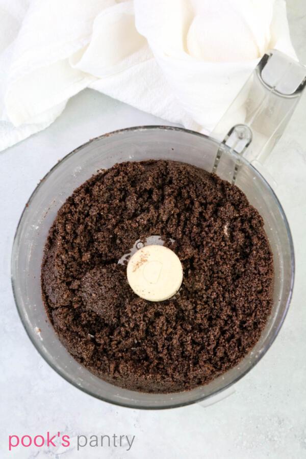 Chocolate graham cracker crumbs in food processor bowl.