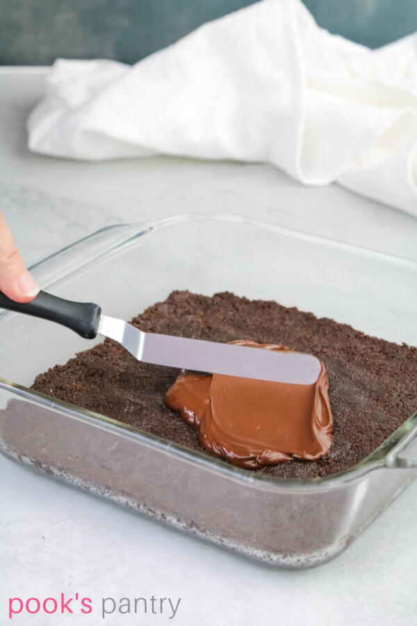 Spreading a thin layer of melted chocolate on top of crust in pan.