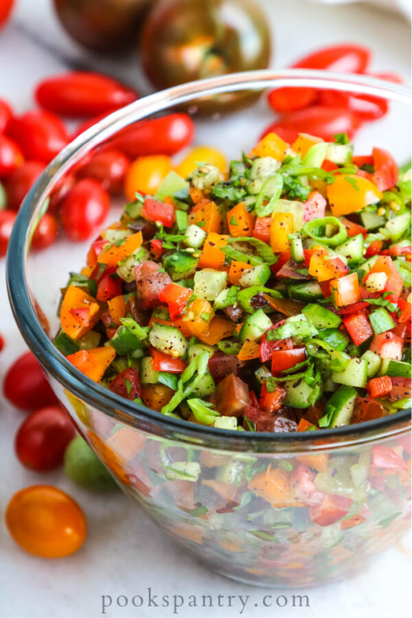 Israeli salad of tomatoes, cucumbers and peppers in clear glass bowl.