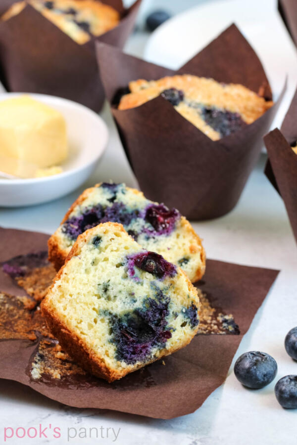 Muffin on brown paper, cut open, with blueberries.
