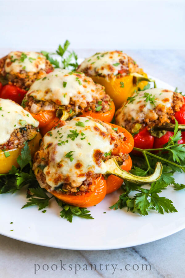 Vegetarian stuffed peppers with quinoa for dinner on a white platter with herbs.