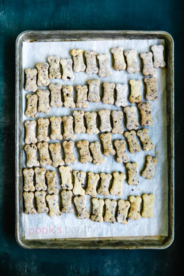 Homemade dog treats on parchment-lined baking sheet.