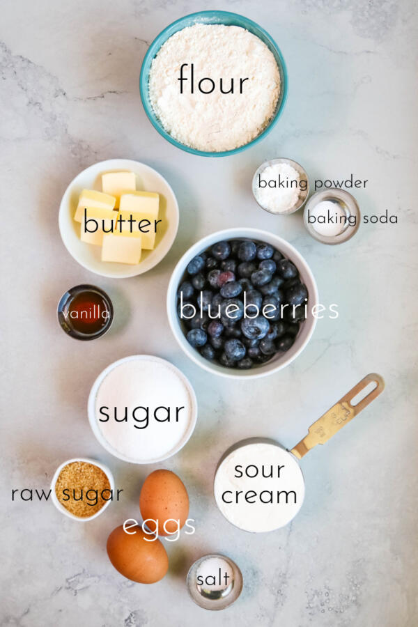 Ingredients for blueberry muffins on marble background.