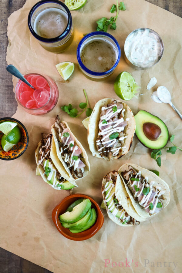Tacos with lime crema, avocado, pickled radish and chicken on butcher paper.