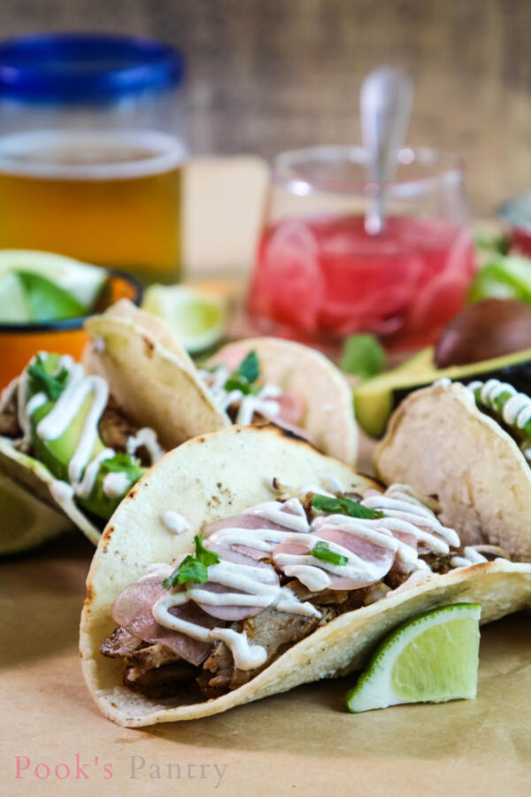 Tacos with grilled chicken and cumin crema on butcher paper with limes and beer in background.