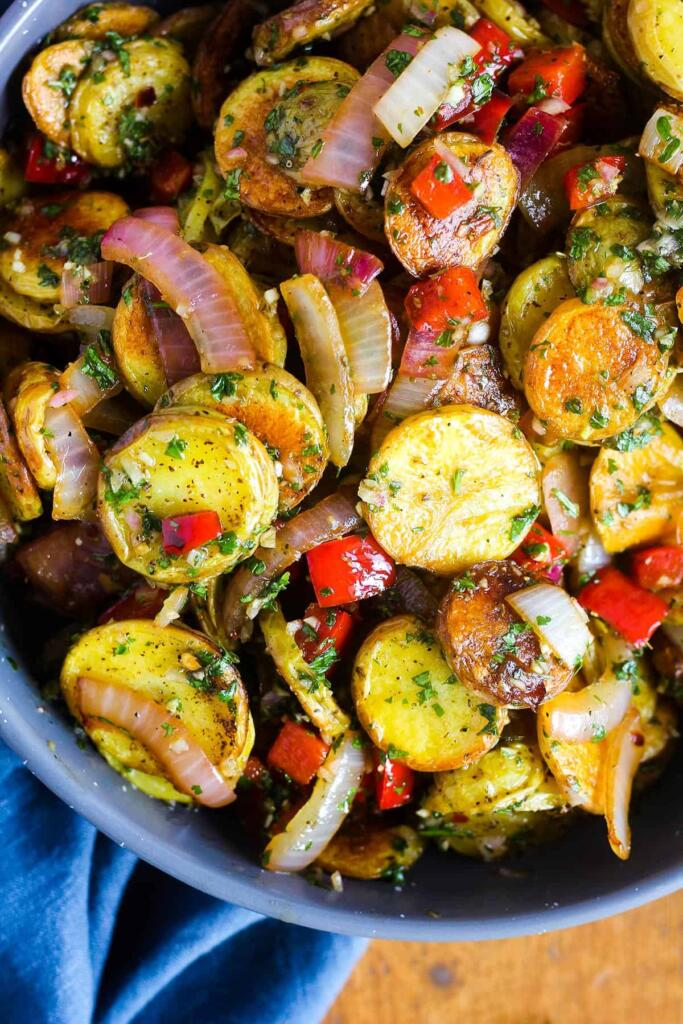 Chimichurri potato salad side dish recipe is bowl with blue towel on the side.
