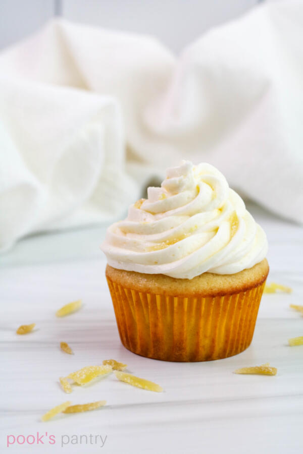 Ginger cupcake with lemon buttercream and candied ginger garnish on white background.