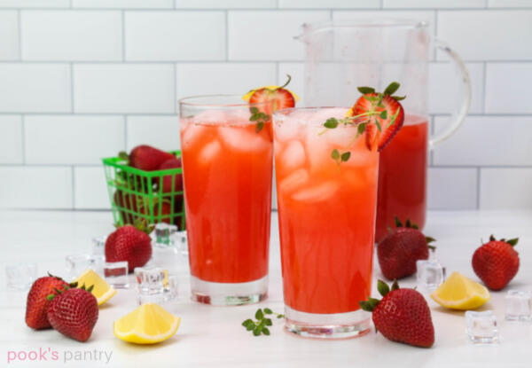 Glasses of strawberry thyme lemonade with basket of strawberries and glass pitcher in the background.