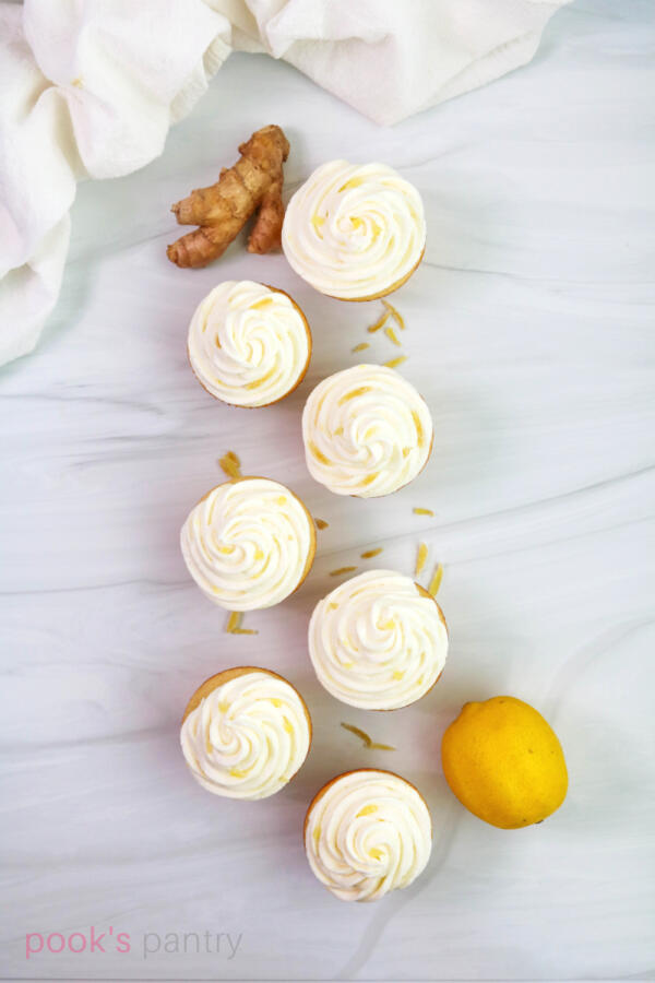 Lemon buttercream on ginger cupcakes with a lemon on the side.