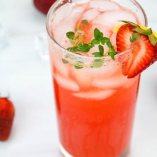 Strawberry thyme lemonade in tall clear glass with fresh strawberry garnish.