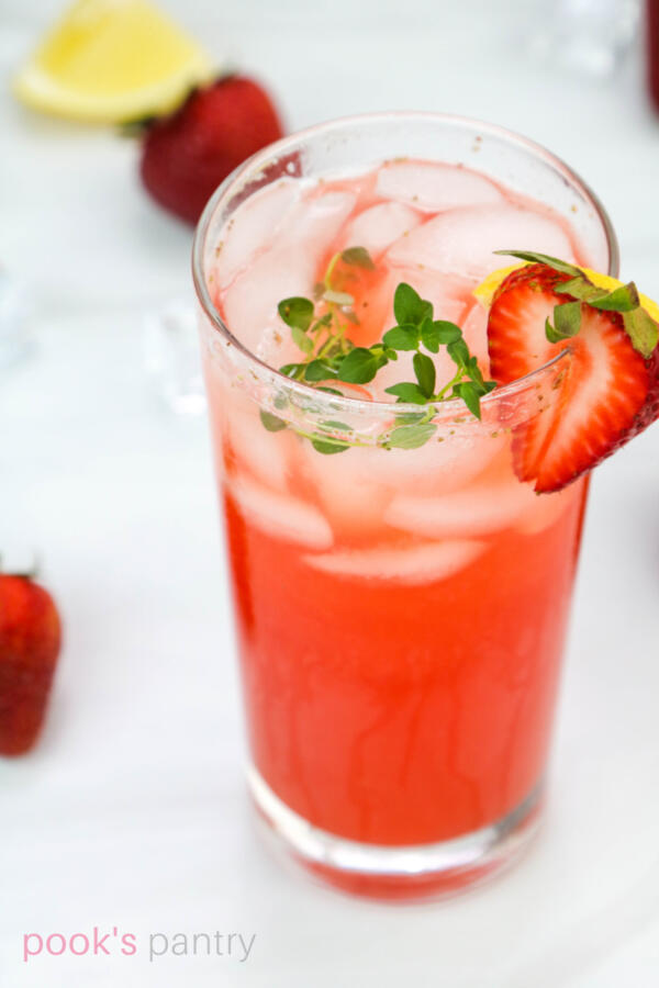 Tall clear glass filled with strawberry thyme lemonade, garnished with slice of strawberry, sprigs of thyme and lemon wedge.