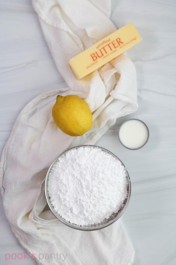 Ingredients for lemon buttercream on white marble background.