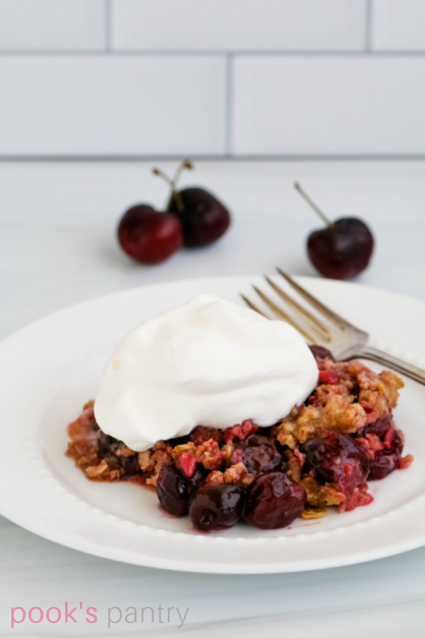 Cherry crisp with whipped cream on white plate with antique fork next to it.