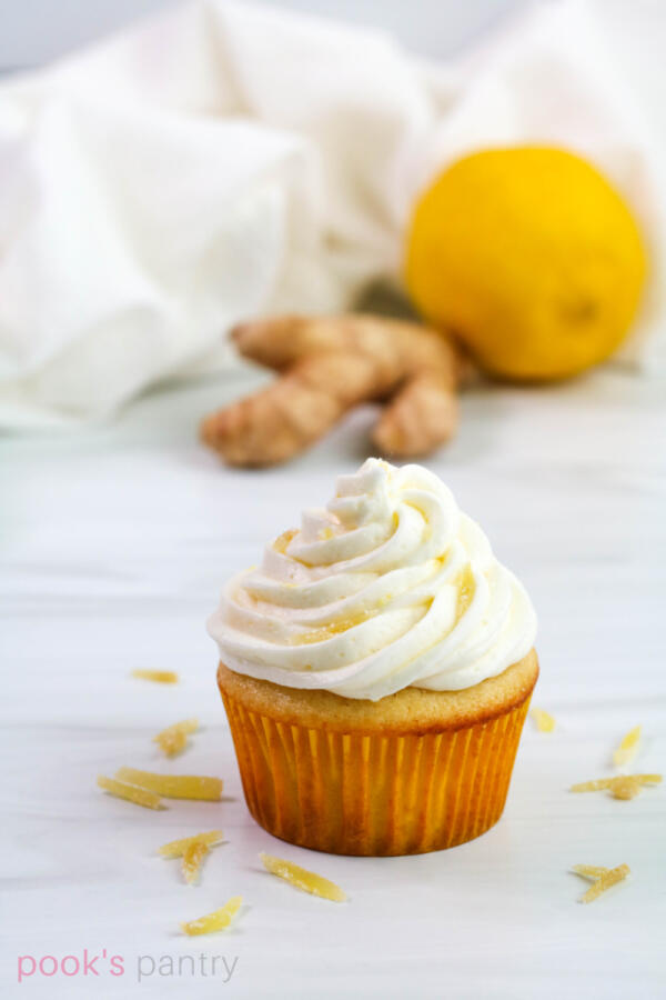 Ginger cupcake frosted with lemon buttercream, garnished with candied ginger. Small hand of ginger and one lemon in the background.