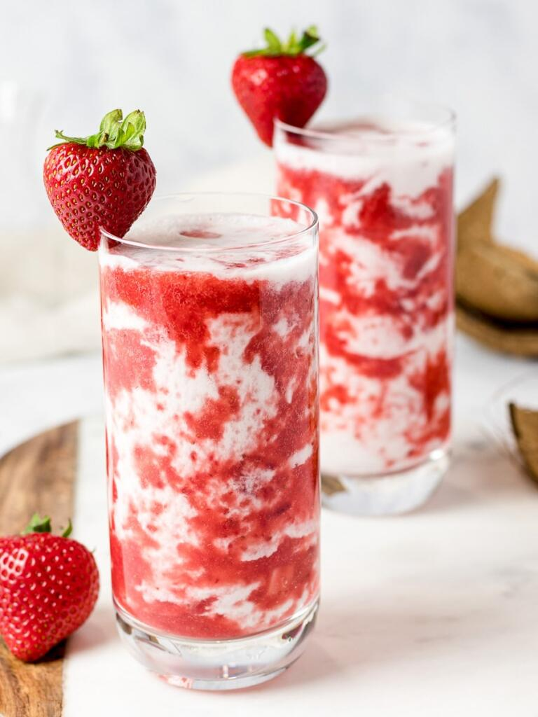 Fresh strawberry milk with whole strawberries on rim of glass.